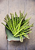 Fresh green asparagus stalks in a dish