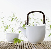 A Japanese teapot and a tea bowl on bamboo sticks