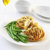 Chicken breast wrapped in puff pastry with garlic sauce and green beans
