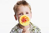 Boy holding large lollipop
