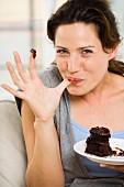 Frau nascht Schokoladenkuchen auf dem Sofa