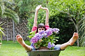 Woman with hydrangea in wheelbarrow