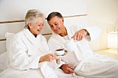 Older couple drinking a morning cup of tea in bed