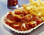Curried sausage with chips on a paper plate