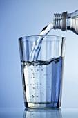 Wasser aus Flasche in Glas einschenken