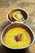 Cream of pumpkin soup with rosemary orange juice and prawn ravioli