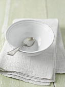 A white bowl with a spoon on a linen cloth