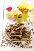 Tray-bake slices with caramel, plums, almonds and chocolate