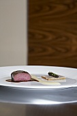 Venison with onion cream and toast with Lardo