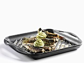 Baltic Sea herring with herb butter in a grill pan