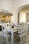 A dining table and chairs made of carved, white painted wood with a view through an archway into a living room