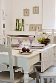 A white wooden table laid with ceramic wine glasses