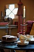 Kaffee und Kuchen mit Kerzenhalter und brennender Kerze auf Tisch