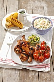Grilled chicken legs with cherry tomatoes, coleslaw and corn cobs