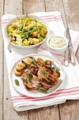 Grilled pork shops with a mustard dip and a potato and bean salad