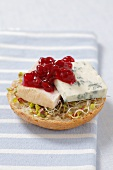 Half a bread roll topped with bean sprouts, blue cheese and cranberry compote