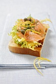 A slice of toast topped with salad, salmon and capers