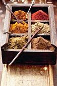Various spices in a wooden box with spoons (Arabia)