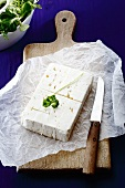 Feta cheese and a knife on a slice of paper on a wooden board