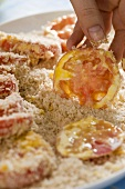 Tomato slices being dusted in breadcrumbs