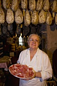 A woman carrying a plate of sliced culatello