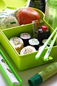 A box of sushi with wasabi and soy sauce
