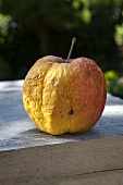 A withered apple on a wooden box