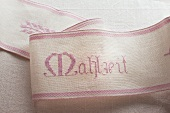 A ribbon embroidered with the word 'Mahlzeit'