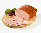 Sliced burgundy ham on a wooden plate