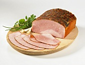 Sliced herb ham on a wooden plate