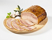 Sliced cold roast ham on a wooden plate