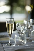 A glass of champagne and a glass of water on a laid table
