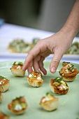 A hand reaching for a salmon and avocado tartlet