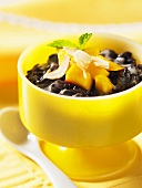 Stick black rice pudding in a yellow bowl