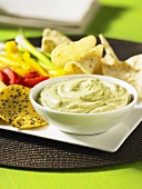 Avocado dip with crisps and fresh vegetables