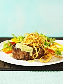 Beef fillet with fried onions and a side salad