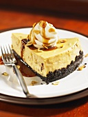 A slice of coffee cheesecake with cream and caramel sauce