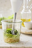 Pesto ingredients being mixed with a hand blender