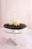 A festive chocolate cake with silver balls, candles and the number 9
