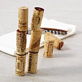 A stack of wine corks, a corkscrew and a cloth