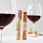 Two stack of wine corks between two glasses of red wine