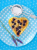 A heart-shaped blueberry pancakes with icing sugar and lavender flowers