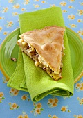 A slice of apple pie with nuts