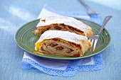 Two slices of apple strudel with hazelnuts, raisins and icing sugar