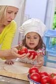 Mutter und Tochter mit Tomaten und Pizzateig