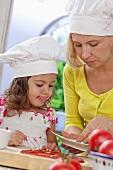 Mutter und Tochter belegen ungebackene Pizza