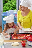 A mother and daughter placing toppings on a pizza