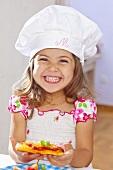 Lachendes kleines Mädchen hält Minipizza