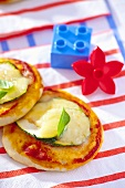 Mini pizzas topped with courgette, cheese and basil