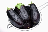 Three aubergines in sieve